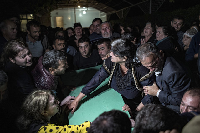Family members mourn over the coffin of Parviz Orucoglu, a 29 year-old Azerbaijani Turk killed with three others in a shelling in a cemetery by Armenian forces, in the city of Tartar, Azerbaijan, Thursday, October 15, 2020. (Photo by Can Erok/DHA via AP Photo)