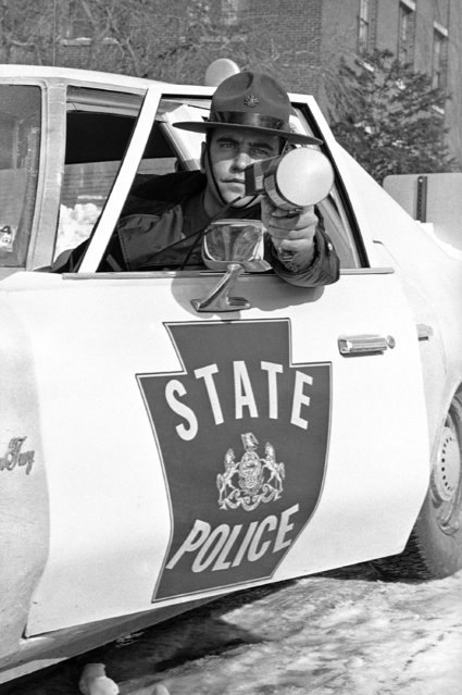 Pennsylvania State Police Trooper A. J. Probst leans out of window of his patrol car displaying the new portable radar unit in Harrisburg, Pa., on January 25, 1978 the state police will use starting February 1. The new units are expected to be more effective than previous models. The radar gun can operate in both directions and records speed on back of unit which is hand held. (Photo by Paul Vathis/AP Photo)