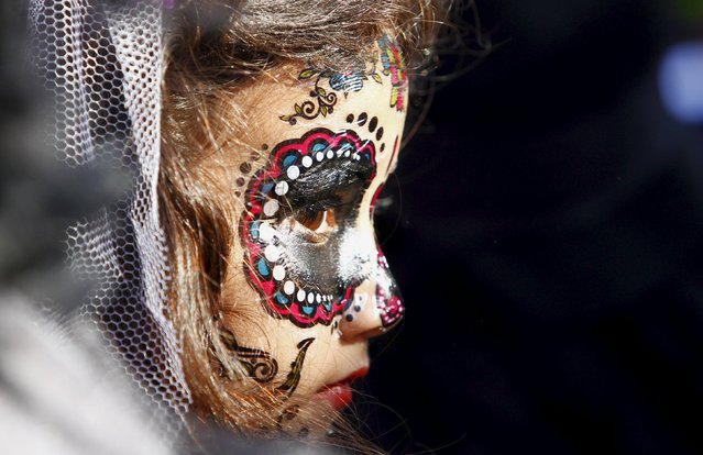 """A girl, with her face painted to look like the popular Mexican figure called """"Catrina"""" also known as """"The Elegant Death"""", participates in a contest at her kindergarten as part of the Day of the Dead celebrations in Tijuana, Mexico, October 29, 2015. On the Day of the Dead, Mexicans pay homage to their dead relatives by preparing meals and decorating their graves. (Photo by Jorge Duenes/Reuters)"""