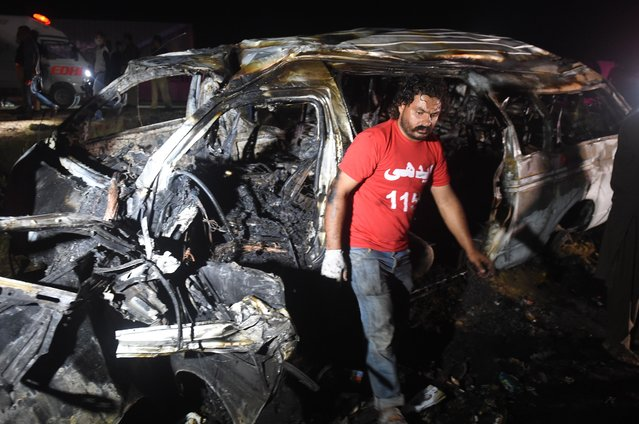 A volunteer walks past a burnt passenger van following an overnight accident in the Nooriabad area on a highway some 50 kilometers from Pakistan's port city of Karachi late on September 26, 2020. At least 13 people were killed and several others injured when a passenger van overturned and caught fire on a highway, local media reported. (Photo by Rizwan Tabassum/AFP Photo)