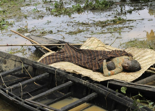 Bodies of flood victims lie in a boat after they were found in floodwater at Balbala village in Goalpara district in the northeastern Indian state of Assam, in this September 24, 2014 file photo. (Photo by Reuters/Stringer)