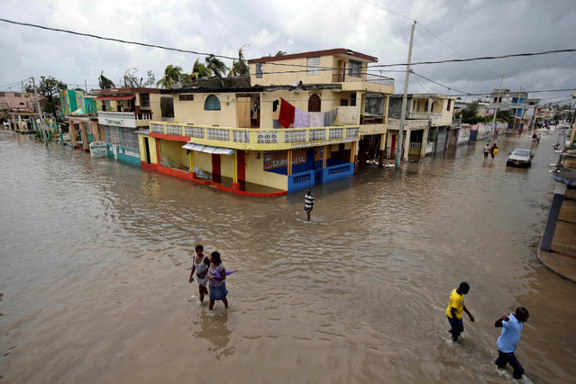 People walk in a flooded area after Hurricane Matthew in Les Cayes, Haiti, October 5, 2016. (Photo by Andres Martinez Casares/Reuters)