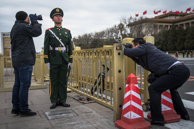 """People take photos of a Chinese People's Liberation Army (PLA) soldier standing guard before the closing of the First Session of the 13th Chinese People's Political Consultative Conference (CPPCC) National Committee at the Great Hall of the People (GHOP) in Beijing, China, 15 March 2018. The CPPCC is the top advisory body of the Chinese political system and runs alongside the annual plenary meetings of the 13th National People's Congress (NPC), together known as """"Lianghui"""" or """"Two Meetings"""". (Photo by Roman Pilipey/EPA/EFE)"""