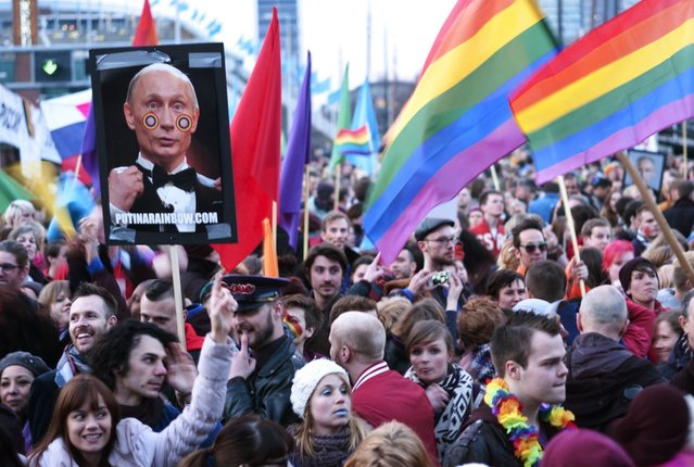 A demonstrator holds up a picture depicting Russian President Vladimir Putin with rainbow circles on his face, during a protest by the gay community in Amsterdam April 8, 2013. Putin is on one-day visit in the Netherlands for the start of the Netherlands-Russia Year. (Photo by Cris Toala Olivares/Reuters)
