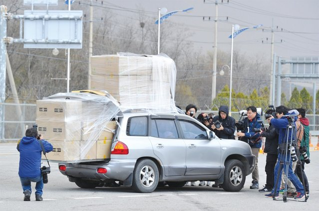 Members of South Korea's media surround a car filled with workers returning from the Kaesong Industrial Park with boxes loaded on top of their car at a gate of the inter-Korean transit office in the border city of Paju, on April 9, 2013. North Korean workers failed to show on April 9 at the Kaesong joint industrial zone, a day after Pyongyang said it was withdrawing labour and suspending operations at the Seoul-funded complex. (Photo by Kim Jae-Hwan)
