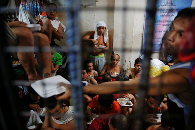 People at a detention cell enjoy their meal brought by a charity organisation to a police station in Manila, Philippines, October 7, 2016. (Photo by Damir Sagolj/Reuters)