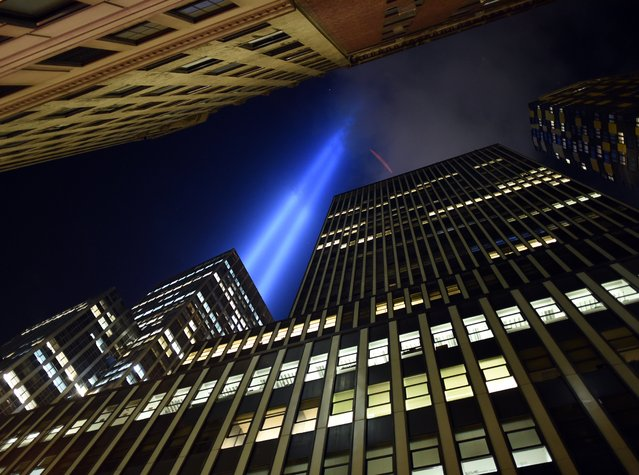 "The ""Tribute in Light"" illuminates the sky  down in the Wall Street area of lower Manhattan in New York on September 10, 2014 on the night before the 13th anniversary of the September 11, 2001 attacks. The tribute, an art installation of the Municipal Art Society, consists of 88 searchlights placed next to the site of the World Trade Center creating two vertical columns of light in remembrance of the 2001 attacks. (Photo by Timothy A. Clary/AFP Photo)"