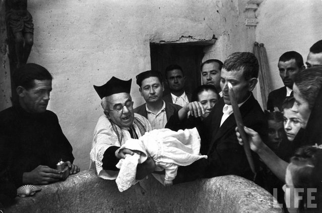 While his godfather holds him over a font, the priest Don Manuel dries the head of month-old Buenaventura Jimenez Morena after his baptism at village church. (Photo by W. Eugene Smith/Time & Life Pictures)