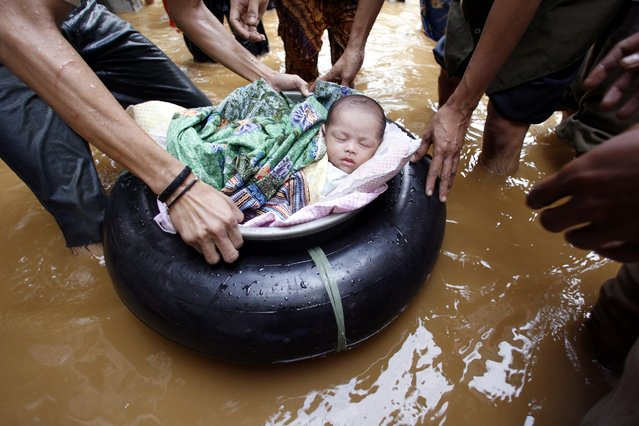 Residents evacuates a two-week old baby from a flooded area in east Jakarta in this February 4, 2007 file photo. (Photo by Enny Nuraheni/Reuters)