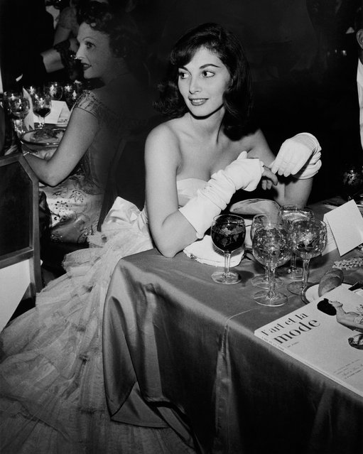 Actress Pier Agnelli wearing a strapless gown and gloves, with unidentified woman in background, at the Franco-American ball at the Waldorf Astoria in New York city on July 1, 1954. (Photo by Nick De Morgoli/Condé Nast via Getty Images)