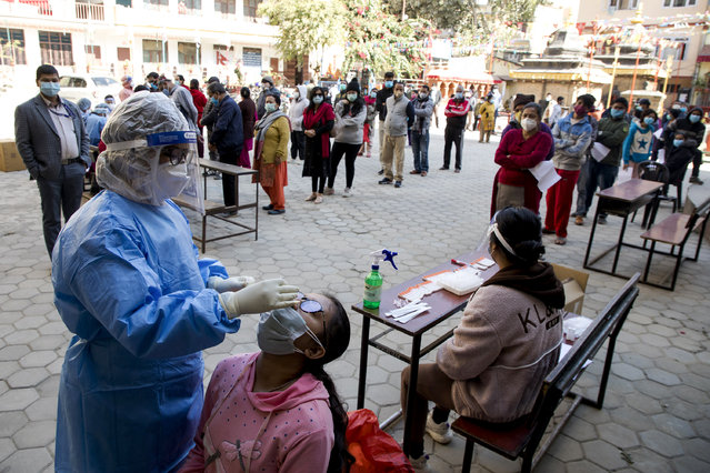 A Ministry of Health staff collects a nose swab sample for an antigen test amid the ongoing coronavirus COVID-19 pandemic at Kathmandu, Nepal, 02 December 2020. According to local media the test is newly launched at the government level to detect COVID-19 infection in the community. Results will be available within 30 minutes which makes this test much more easier. (Photo by Hemanta Shrestha/EPA/EFE/Rex Features/Shutterstock)