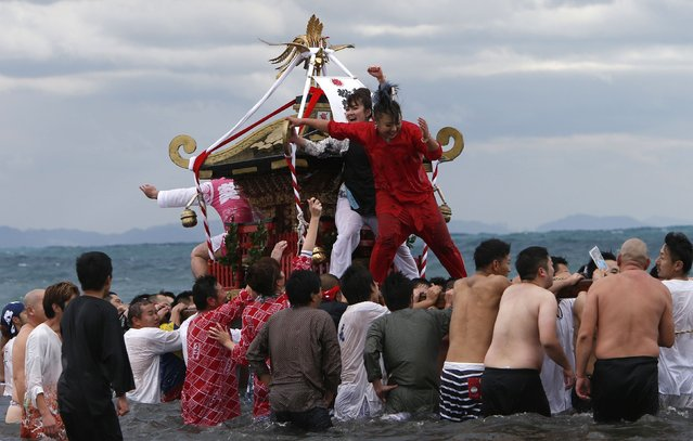 "Women riding on a ""mikoshi"" or portable shrine cheer on carriers as they carry the shrine into the sea during a festival to wish for calm waters in the ocean and good fortune in the new year in Oiso, west of Tokyo, January 1, 2015. (Photo by Yuya Shino/Reuters)"