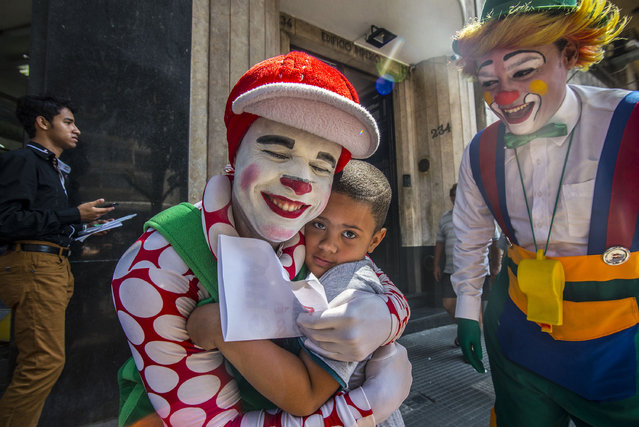 A clown hugs a child during a protest with a group of clowns in the old center of Sao Paulo, Brazil on October 24, 2016. (Photo by Cris Faga via ZUMA Wire)