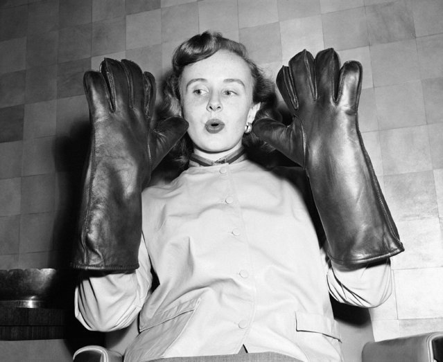 "Florence Brown of the Department of Commerce, gives with an ""Oh, look what I've got"" expression as she holds up a pair of lead impregnated atomic gloves at the leather exhibition in Washington, February 23, 1954. The gloves are just the thing if you want to split an atom and have the $60 to pay for them. The jacket she is wearing is not atomic attire it is part of a leather suit costing $95. (Photo by William J. Smith/AP Photo)"