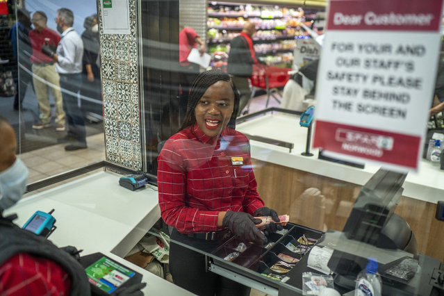 In this March 30, 2020, photo, Zandile Mlotshwa, 21, cashier at Spar supermarket in the Norwood suburb of Johannesburg, counts her cash at the end of her shift. From South Africa to Italy to the U.S., grocery workers – many in low-wage jobs – are manning the front lines amid worldwide lockdowns, their work deemed essential to keep food and critical goods flowing. (Photo by Jerome Delay/AP Photo)