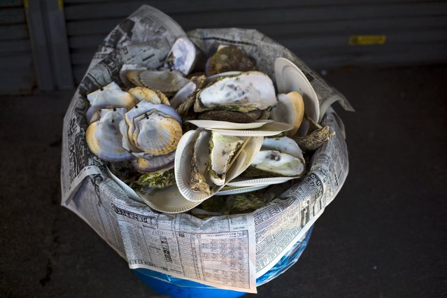 Empty clam shells pile up in a bin behind a seafood stall in the outer part of the Tsukiji fish market, the Jogai Shijo, in Tokyo January 4, 2015. (Photo by Thomas Peter/Reuters)