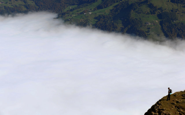 A hiker stands above the fog near the peak of Mount Rigi, Switzerland at 1,797 m (5,896 ft) above sea level October 16, 2016. (Photo by Arnd Wiegmann/Reuters)