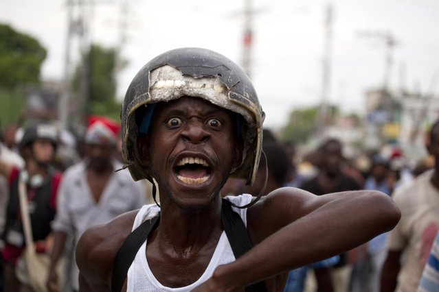 A demonstrator wearing a derelict motorcycle helmet yells anti-government slogans during a protest against the official election results, in Port-au-Prince, Haiti, Thursday November 26, 2015. Demonstrators are claiming fraud and are demanding that the Oct. 25 first-round presidential election where the top two finishers are government-backed candidate Jovenel Moise and former state construction chief Jude Celestin, be annulled. (Photo by Dieu Nalio Chery/AP Photo)