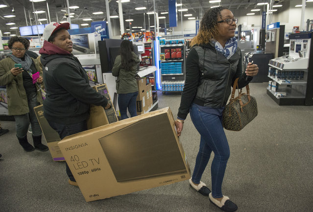 (L-R) Mariecia Wilkinson and sister Makima Wilkinson drag their 40 and 50 inch flat screen tv's through the store at the Black Thursday sale at the Best Buy in Alexandria, VA on November 26, 2015. Retailers seem freshly optimistic about the importance and durability of brick-and-mortar stores in the e-commerce era. It turns out, many years into the online shopping revolution, there are just some things that shoppers prefer to touch, feel and test before they buy them. (Photo by Linda Davidson/The Washington Post)