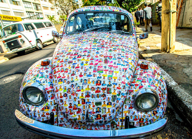 A car decorated with stickers from the 2018 World Cup is seen in Sao Paulo, Brazil on May 25, 2018. The owner of the World Cup Sticker car said that his friends glued 15,000 stickers from the 2018 World Cup album on his car and he decided to leave them until the end of the cup. (Photo by Cris Faga/Rex Features/Shutterstock)