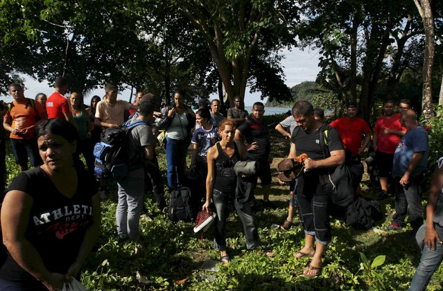 Cubans Migrants stand after arriving safely in La Miel in the province of Guna Yala in Panama, having crossed the border from Colombia through the jungle, November 28, 2015. Scores of Cubans have come to shore at a remote outpost in Panama near the Colombian border as they seek overland passage towards the United States fearing a recent detente between Washington and Havana could end their preferential treatment. (Photo by Carlos Jasso/Reuters)
