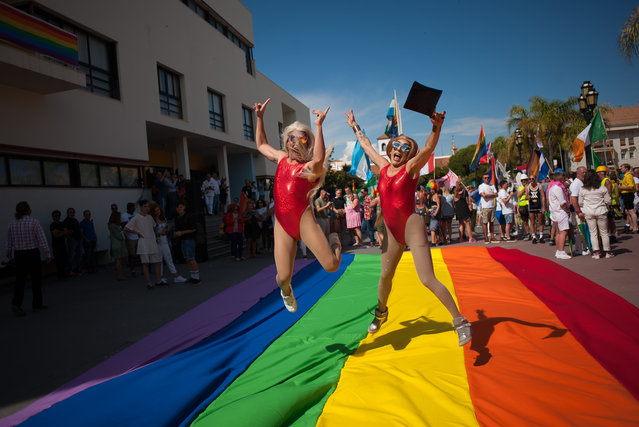 """Two mens in costume are seen jumping on a large pride gay flag before the start the Pride LGTB Torremolinos 2018. Torremolinos celebrates this week the LGBT Pride 2018 under the slogan: """"Fifty years being visible"""", which commemorates the fight of the gays, lesbians, transgender, bisexuals and intersexuals for their rights. (Photo by Jesus Merida/SOPA Images/LightRocket via Getty Images)"""
