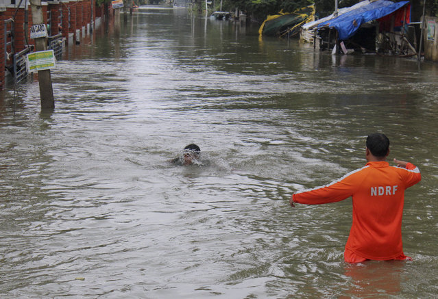 A National Disaster Response Force person, right, arrives to rescue a boy who fell while wading through flood waters in Chennai, India, Thursday, December 3, 2015. The heaviest rainfall in more than 100 years has devastated swathes of the southern Indian state of Tamil Nadu, with thousands forced to leave their submerged homes and schools, offices and a regional airport shut for a second day Thursday. (Photo by AP Photo)
