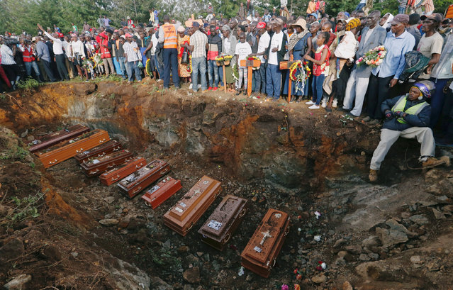 Coffins are seen arranged inside a mass grave during the burial of people killed when a dam burst its walls, overrunning nearby homes, in Solai town near Nakuru, Kenya May 16, 2018. (Photo by Thomas Mukoya/Reuters)