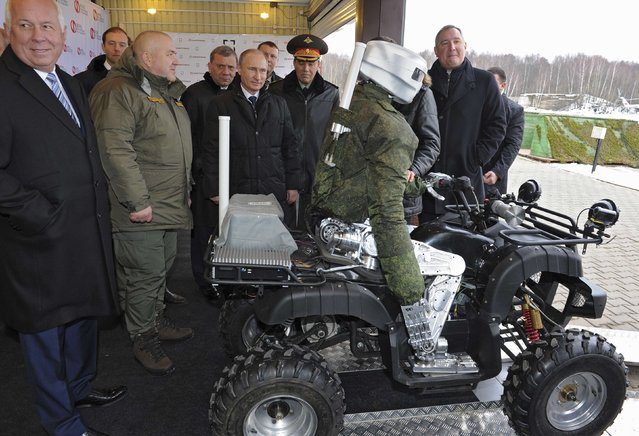 "Russia's President Vladimir Putin (C) looks at a human-like combat robot during a visit to the Central Research Institute for Precision Machine (""Tochmash"") in Klimovsk, outside Moscow, January 20, 2015. (Photo by Mikhail Klimentyev/Reuters/RIA Novosti/Kremlin)"