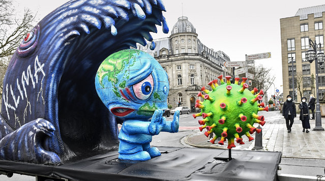 A political carnival float depicting climate and coronavirus crisis is driving in the streets of Duesseldorf Duesseldorf, Germany, Monday, February 15, 2021. (Photo by Martin Meissner/AP Photo)