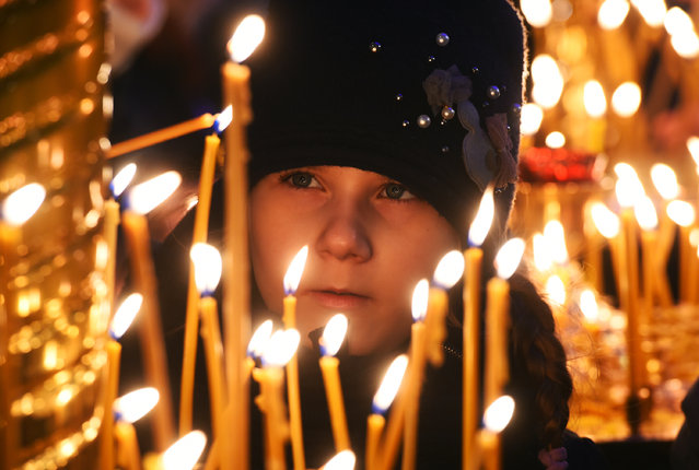 A girl lights a candle during a Christmas service in Kazan Cathedral in central Saint Petersburg, on January 6, 2021. Orthodox Christians celebrate Christmas on January 7 in the Middle East, Russia and other Orthodox churches that use the old Julian calendar instead of the 17th-century Gregorian calendar adopted by Catholics, Protestants, Greek Orthodox and commonly used in secular life around the world. (Photo by Olga Maltseva/AFP Photo)