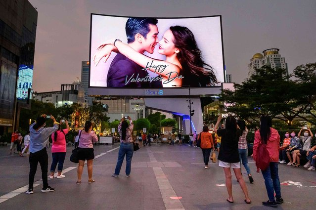People take photographs of a screen wishing a happy Valentine's day, in Bangkok, Thailand on February 14, 2021. (Photo by Mladen Antonov/AFP Photo)