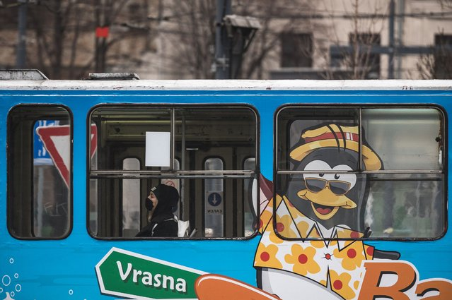 A commuter wears a protective face mask during a tram ride during the COVID-19 pandemic in Belgrade, on December 14, 2020. Serbia is witnessing a rise in coronavirus infections prompting the government to consider new restrictions. (Photo by Andrej Isakovic/AFP Photo)