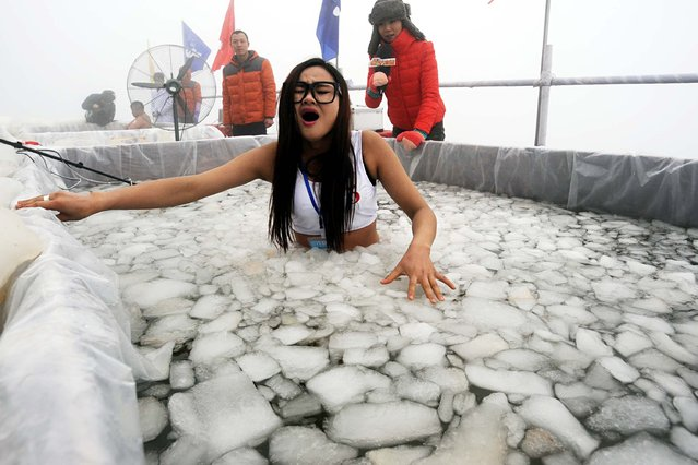 This picture taken on January 25, 2015 shows a participant taking part in an ice water challenge in Zhangjiajie, central China's Hunan province. Participants were required to stay in an ice pond, holding an ice block while eating ice-cream with an electric fan blowing at them. (Photo by AFP Photo/Stringer)