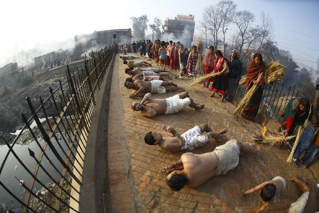 Devotees offer prayer by rolling on the street during the final day of the month-long Swasthani festival of Bhaktapur, near Kathmandu, February 3, 2015. During the festival, devotees recite one chapter of a Hindu tale daily from the 31-chapter sacred Swasthani Brata Katha book, that is dedicated to God Madhavnarayan and Goddess Swasthani, alongside various other gods and goddesses and the miraculous feats performed by them. (Photo by Navesh Chitrakar/Reuters)