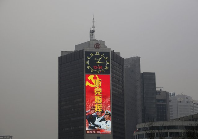 A large screen on a building shows a propaganda image of the Chinese People's Liberation Army on a heavily polluted day in Beijing, December 26, 2015. (Photo by Kim Kyung-Hoon/Reuters)