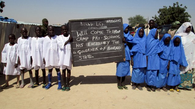 Schoolchildren, who are among internally displaced people camped at Dikwa, Borno State, hold a sign during a visit by Borno State Governor Kashim Shettima, at the camp in Borno, Nigeria December 27, 2015. (Photo by Reuters/Stringer)