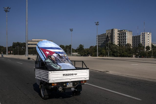 A pickup truck, hauling a poster of Fidel Castro, drives past Revolution Square completely empty of tourists, in Havana, Cuba, Tuesday, March 2, 2021. The Caribbean is hunting for visitors and vaccines to jump-start the stalled economy in one of the world's most tourism-dependent regions. (Photo by Ramon Espinosa/AP Photo)