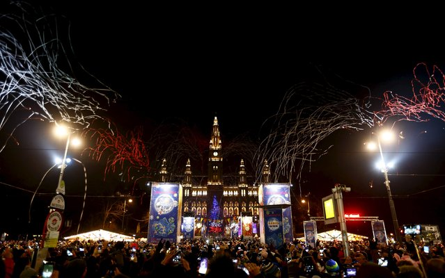 Revellers watch as confetti explodes in front of Vienna's city hall as Austria's capital ushers in the New Year, January 1, 2016. (Photo by Leonhard Foeger/Reuters)