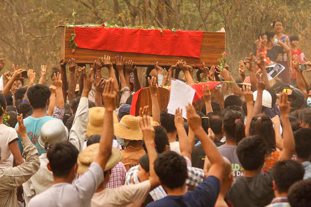 This photo taken and received from an anonymous source via Facebook on March 29, 2021 shows mourners making the three-finger salute during the joint funerals of three protesters, who were shot dead the day before amid a crackdown by security forces on demonstrations against the military coup, in Monywa, Sagaing region. (Photo by Handout/Facebook/AFP Photo)