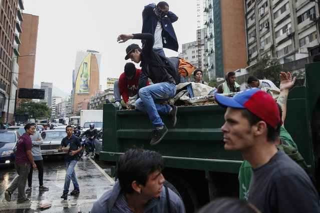Opposition students block an avenue with a truck loaded with rocks as they protest against President Nicolas Maduro's government in Caracas February 12, 2015. Venezuelan troops blocked students during marches against Maduro on Thursday as pro-government supporters also rallied on the anniversary of 2014 protests that led to 43 deaths. (Photo by Jorge Silva/Reuters)