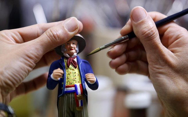 A worker paints a santon, the typical figurines from Provence, at the Marcel Carbonel's Santon factory in Marseille, November 28, 2016. Santons are traditional hand-colored figurines usually set in Christmas Nativity scenes. (Photo by Jean-Paul Pelissier/Reuters)