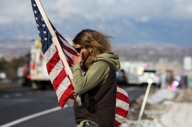 A man reacts while watching a procession of police vehicles approaching the memorial service for slain Boulder Police Officer Eric Talley, who was killed during a mass shooting on March 22 at King Soopers grocery store, in Lafayette, Colorado, U.S., March 30, 2021. (Photo by Jim Urquhart/Reuters)