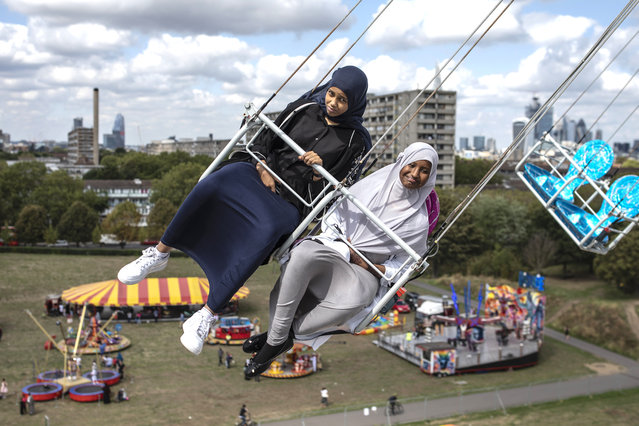 Children enjoy a ride during an Eid in the Park celebration marking the start of Eid Al-Adha at Burgess Park on August 21, 2018 in London, England. The traditional four-day celebratory festival marks one of the holiest days in the Islamic religious calendar. (Photo by Dan Kitwood/Getty Images)