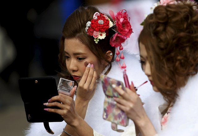 Japanese women wearing kimonos apply make up before their Coming of Age Day celebration ceremony at an amusement park in Tokyo January 11, 2016. (Photo by Yuya Shino/Reuters)