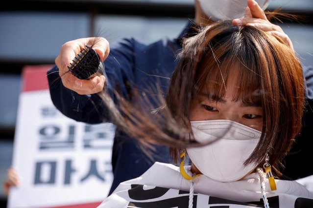 A South Korea university student gets her head shaved during a protest against Japan's decision to release contaminated water from its crippled Fukushima nuclear plant into the sea, in front of the Japanese embassy, in Seoul, South Korea, April 20, 2021. (Photo by Kim Hong-ji/Reuters)