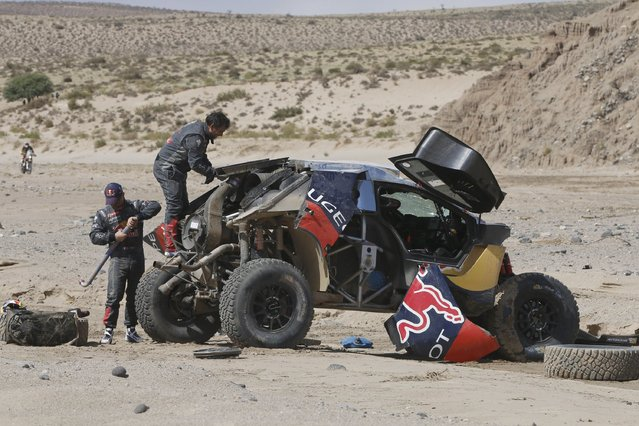 Sebastien Loeb (L) of France and co-pilot Daniel Elena work on their car after an accident which turned the car over during the eighth stage in the Dakar Rally 2016 near Belen, Argentina, January 11, 2016. (Photo by Andre Lavadinho/Reuters)