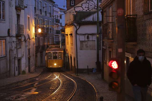 A man wearing a face mask walks up a street as a tram drives by in Lisbon's old Alfama neighborhood, Thursday, February 4, 2021. A pandemic surge in January thrust Portugal into the spotlight as world's worst-hit country by size of population, according to Johns Hopkins University data, while it's vaccine program has inspired hope amid an extended lockdown. (Photo by Armando Franca/AP Photo)