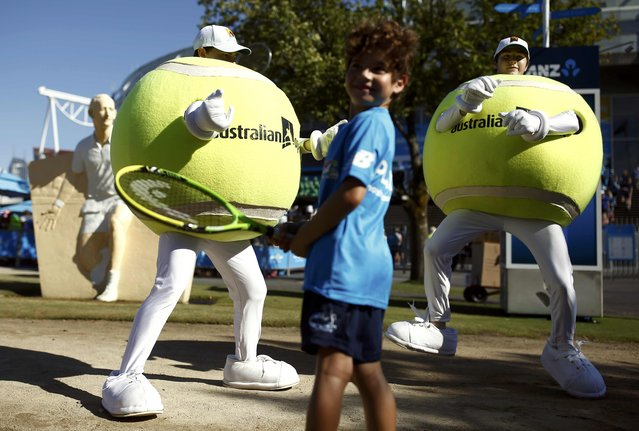 A boy smiles in front of performers dressed in tennis ball outfits before the start of the Australian Open tennis tournament at Melbourne Park, Australia, January 18, 2016. (Photo by Thomas Peter/Reuters)