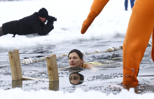 A woman swims in icy waters of a lake during celebrations of Orthodox Epiphany in Minsk, January 19, 2016. (Photo by Vasily Fedosenko/Reuters)